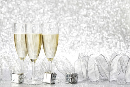 Champagne glasses and christmas decoration on silver bokeh background photo