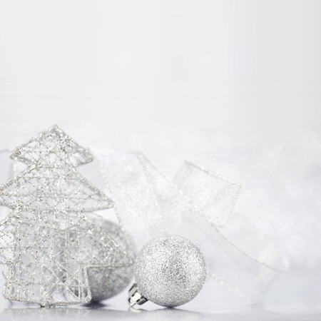 Christmas decorative fir and balls on light silver bokeh background photo