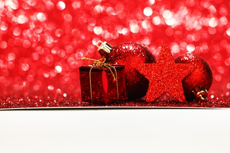Red Christmas gift and decoration on shiny glitter background photo