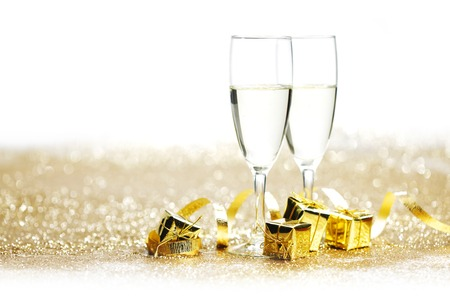 Champagne glasses and gifts on glitters with white copy space photo