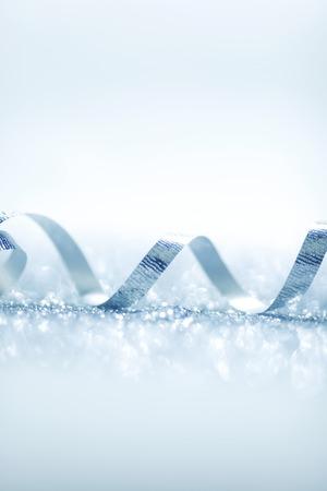 Beautiful glitter silver ribbon tape curl in glitter background photo