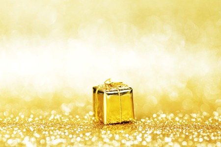 Gold decorative box with holiday gift on abstract gold background photo
