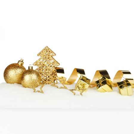 Beautiful various golden christmas decor on snow close-up photo