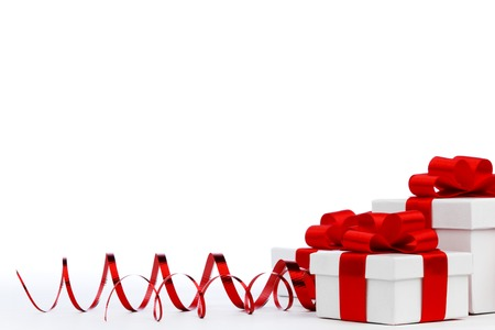 Gifts in white boxes with curly red ribbons isolated on white background photo