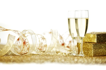 Two elegant flutes of sparkling champagne with decorative golden gifts photo