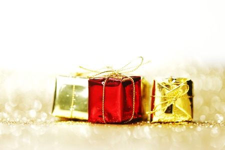 Decorative boxes with holiday gifts on abstract gold background photo