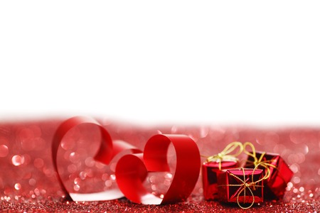 Valentines day ribbon hearts and gifts on decorative glitters, isolated on white photo