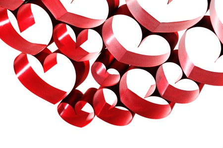 Red ribbons shaped as hearts on white background photo