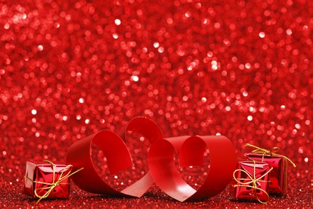 Decorative hearts of red ribbon and gifts on shiny glitter background photo