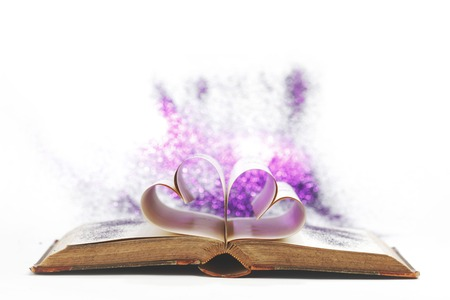 Pages of open book rolled in heart shape isolated on white photo