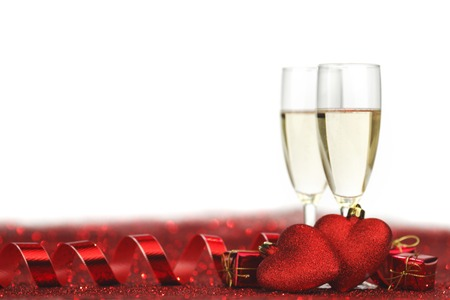 Glasses with Champagne and handmade hearts on red glitters isolated on white background Standard-Bild