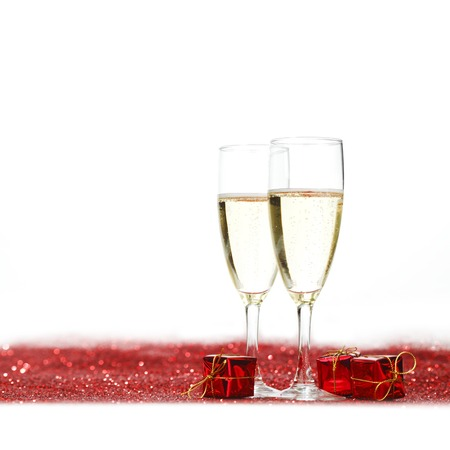 Glasses with Champagne and gifts on red glitters isolated on white background photo