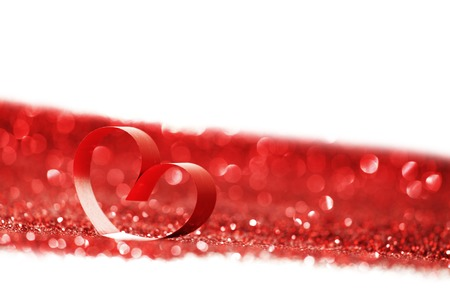 Red ribbon heart on glitters isolated on white, Valentines day concept photo