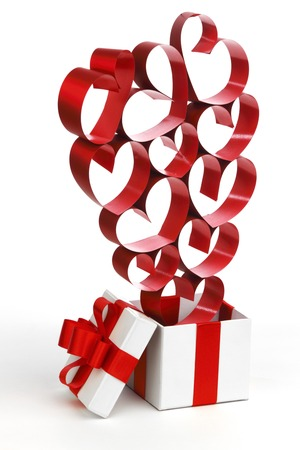 White box with red ribbons and decorative hearts isolated on white background photo