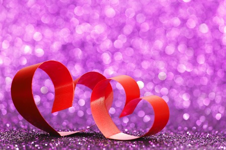 Decorative hearts of red ribbon on shiny glitter background photo
