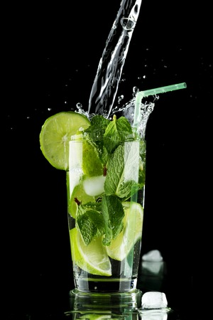 Pouring fresh mojito cocktail in glass isolated on black background photo