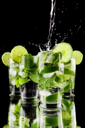 Pouring fresh mojito cocktail in glasses isolated on black background photo