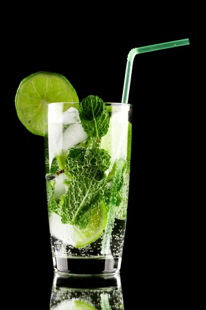 Mojito cocktail with lime, mint and ice on black background photo