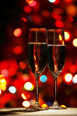 Two champagne glasses on color bokeh background photo