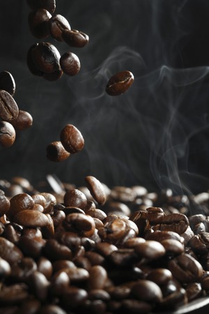 steaming coffee: Falling roasted coffee beans with steam on black Stock Photo