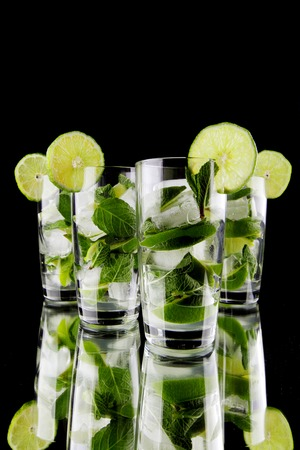 Mojito cocktails with lime and mint on black background photo