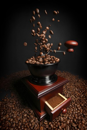 grinder: Vintage manual coffee grinder with falling coffee beans Stock Photo