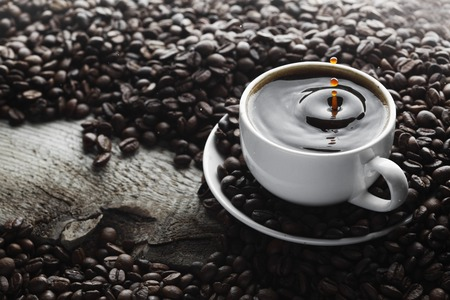 Coffee splash in white cup over roasted coffee beans background photo