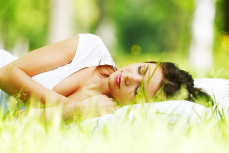 Young woman sleeping on white pillow in fresh spring grass photo