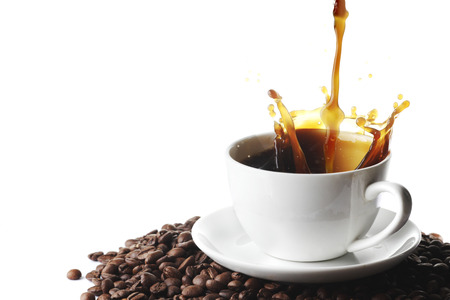 Pouring coffee with splash in cup on coffee beans isolated on white background