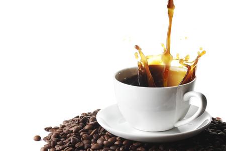 granos de cafe: Verter el café con el chapoteo en taza en granos de café aislados en el fondo blanco Foto de archivo