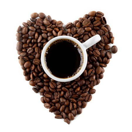 Cup of coffee on coffee beans shaped as a heart isolated on white background photo