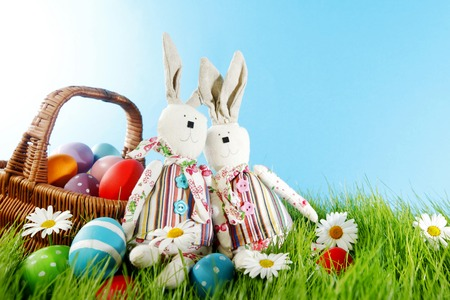 Easter basket with eggs and rabbits on green meadow with flowers photo