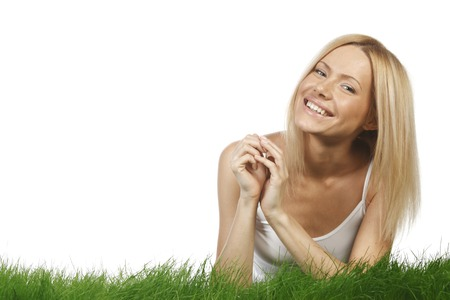 Smiling beautiful woman on grass isolated on white background photo