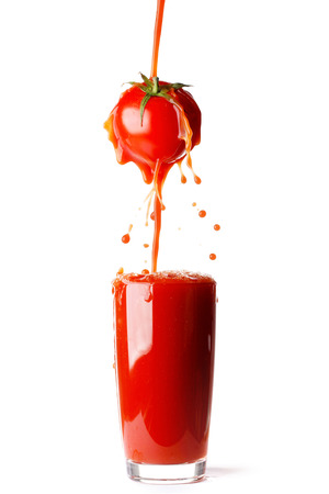 Juice pouring from tomato into glass isolated on white background photo