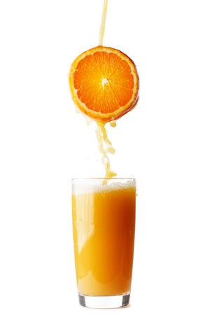 Juice pouring from orange into glass isolated on white background photo