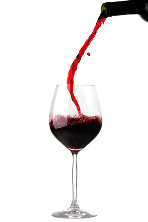 Red wine pouring from bottle into glass isolated on white background
