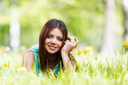 Young beautiful woman with apple resting on fresh green grass with flowers photo