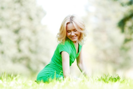 Beautiful young blond woman sitting on grass in park and enjoyng nature photo
