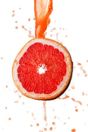 Grapefruit juice splashing on slice isolated on white background photo