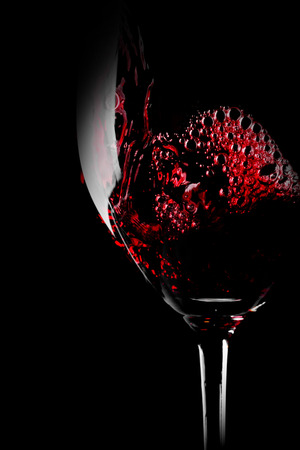 pouring wine: Glass of red wine close-up isolated on black background