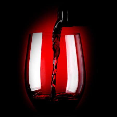 Red wine pouring in glass on dark background photo
