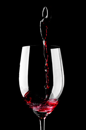Red wine pouring into glass isolated on black background photo