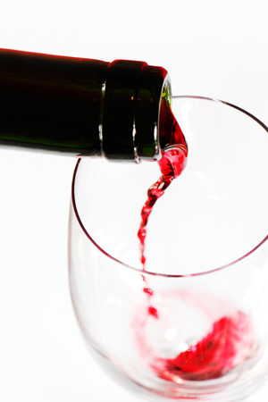 Red wine pouring into glass isolated on white background photo