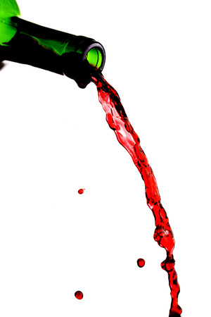 red wine pouring: Red wine pouring from bottle isolated on white background Stock Photo