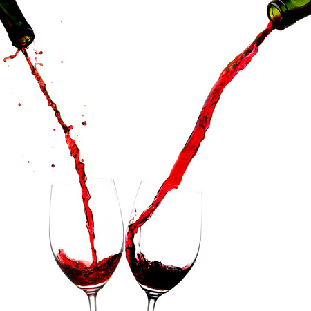 Pouring wine into two glasses isolated on white background photo
