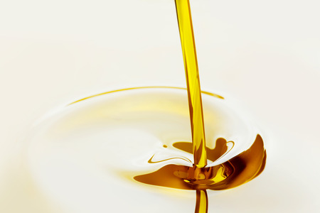 flowing: Pouring liquid golden oil close up view Stock Photo