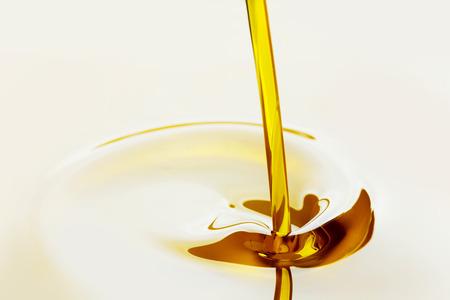 flujo: Verter el aceite dorado l�quido vista de cerca Foto de archivo