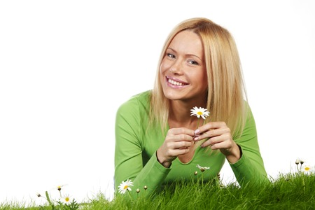 Beautiful young blonde woman lying on grass with chamomile flowers, isolated on white background photo