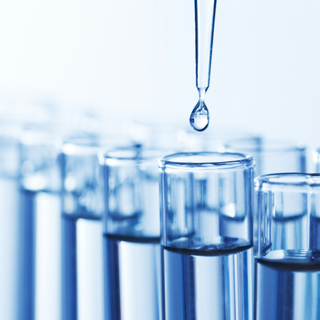 beakers: Laboratory pipette with drop of liquid over glass test tubes in a science research lab