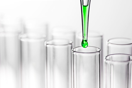 Laboratory pipette with drop of liquid over glass test tubes in a science research lab